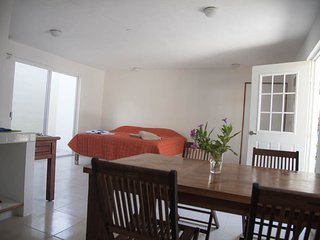Dinning area for 4, king size bed, access to the small private garden and front entrance.