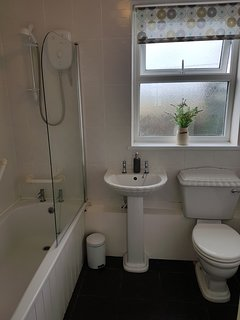 Light, airy bathroom with shower over bath