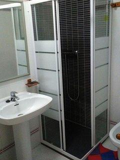 Baño con ducha con mampara, bidet, lavabo y wc