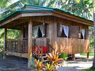 Bamboo cottage with one bedroom, full bathroom, living and dining room, and covered balcony.