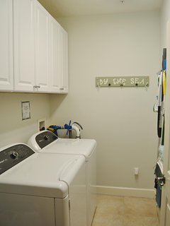 Separate laundry room with laundry supplies, beach towels and umbrella and cleaning supplies should you need them