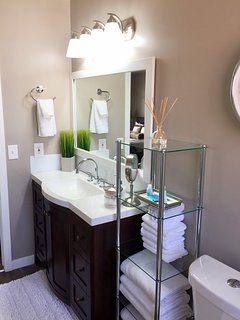 The bathroom is beautiful and bright with plenty of fresh linens.