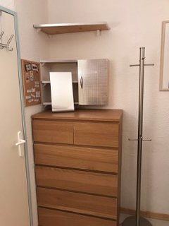 Drawer storage, hanging storage and coat stand in bunk room with mirror.