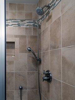 The tiled shower has multiple heads and a bench.
