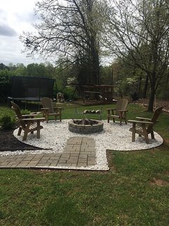 Fire pit area with trampoline and swing set in the background