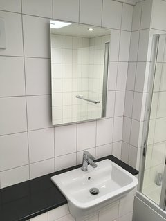 Illuminated dressing mirror and basin inset into vanity unit