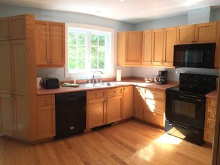 Light streams through the windows of the fully equipped kitchen.
