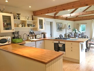 kitchen with electric oven, 5 burner gas hob etc, looking across to the dining and lounging area.