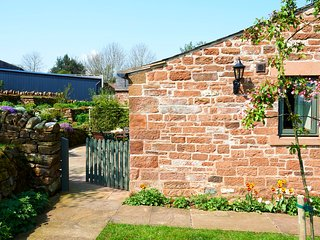 The gated sandstone terrace to the rear of Jennys Croft opens up to raised beds and its rear lawn