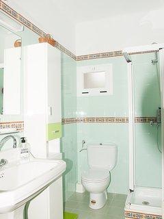 Baño completamente exterior con ducha, equipado con armario, calefactor, felpudo,papel wc, jabón..