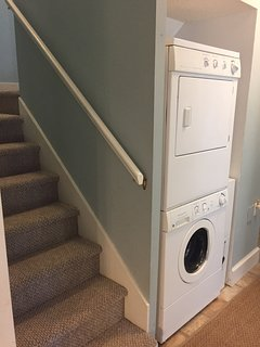 The hall closet holds a stacked washer/dryer.  Head upstairs to the loft bedroom.