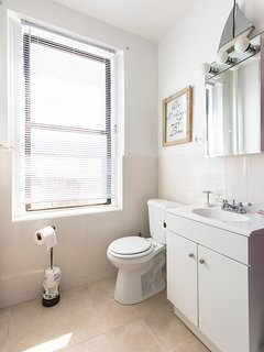 Clean, modern & full family bathroom with dual shower heads and tub access.  Vanity, Tub, Shower