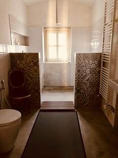 Our bathroom (bagno) is a simple walk in space with rain fall shower and tiled sit down bench seat.
