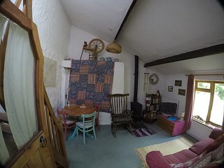 View of living room showing woodstove, table+chairs,settee, rocking chair+even a spinning wheel!