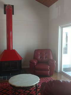 Upper Sitting Room with stove valeted ceilings and waterfront views.