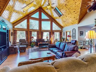 Lakefront home with floor-to-ceiling windows, wraparound deck, & game room