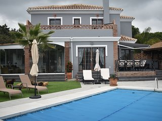View from pool, house now painted in a modern grey colour