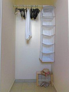 Face à la salle de bain, un espace penderie et rangement pour poser vos valises