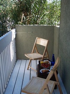 Balcony with table and chairs for enjoying perfect Santa Monica weather.