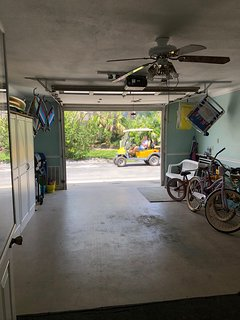 garage with bikes and beach chairs, surfboards, umbrella and toys,