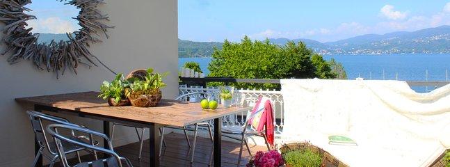 Utsikt från den stora terrassen över bergen och sjön. Bord med sex platser.