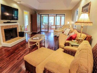 The living room features comfortable furnishings, hardwood floors and a large screen TV.