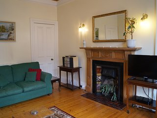 The large living room has many period features including a feature fireplace.