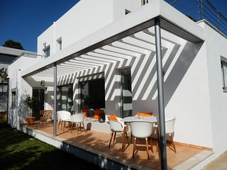 Rear of villa with table and chairs next the pool