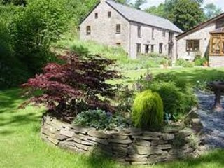 Cwm Mill sits in 1.5 acres of ground next to River Monnow .