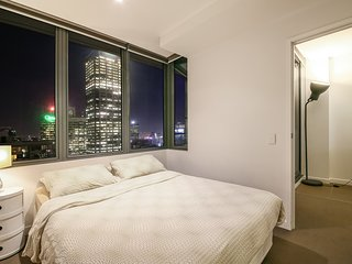 A bedroom with a queen sized bed & a view.