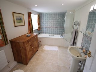 Large ensuite bathroom with bath and over-bath shower