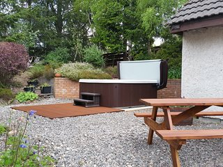 Sunken garden area with hot tub and picnic table