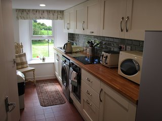 Galley kitchen complete with ceramic hob, oven, microwave, washing machine and fridge freezer.