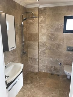 All bathrooms are large a beautifully finished in travertine
