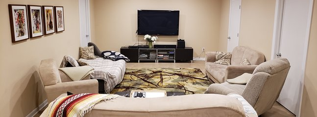 Lower level spacious living room with comfortable chairs, 2 sofa-beds, big screen TV/ BlueRay
