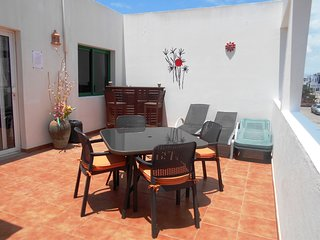 Large sun terrace consisting with 4 sun loungers, bar and alfresco dining table set.