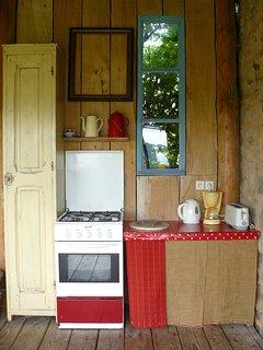 Cuisine d'été avec cafetière, bouilloire, grille pain, cuisinière, frigo.
