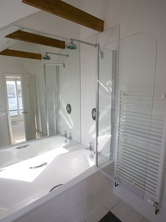 Master bathroom with mirror behind bath reflecting sea view