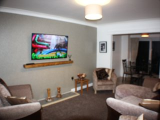 lounge with large wall mounted tv, internet, and seating for  6 guests