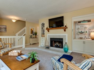 Large living space with flat panel smart TV and plenty of natural light