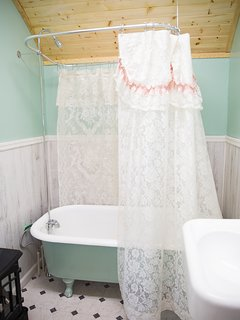 The bathroom has an antique claw foot tub and sink. The tub also has a shower.
