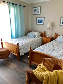 The bedroom has two twin beds. Sliding doors lead to a small porch.
