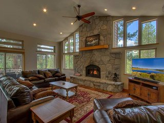 This great room on the top floor is adorned with a huge flatscreen TV, a beautiful stone fireplace, and plenty of windows that let in tons of natural light.
