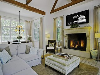 The great room has a comfortable sectional, gas fireplace, flatscreen TV, breakfast nook, and french doors leading to the pool area.