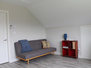 Open plan lounge area with futon couch for a third guest