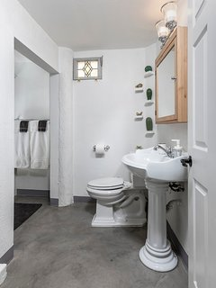 Our uniquely styled bathroom is fresh, light & features original stained glass windows for airflow.