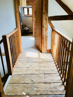 A mezzanine separates the two bedrooms and leads downstairs. The floor is original elm boards