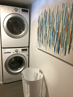 Full size washer and dryer with cleaning supplies included along with an iron and ironing board.