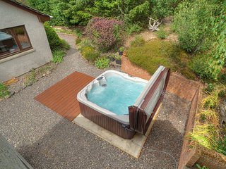View of back garden area and the very private  6 person hot tub, surrounded by raised garden area