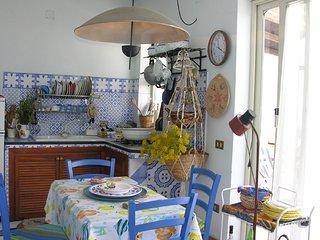 Cucina attrezzata con tutte le stoviglie e lavatrice in terrazza